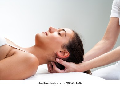 Close up of  chiropractor pressing back of head. Therapist doing healing massage with fingers at back of neck.