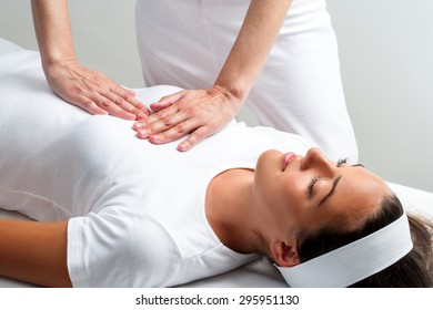 Close up of chiropractor pressing with hands on chest at reiki session.