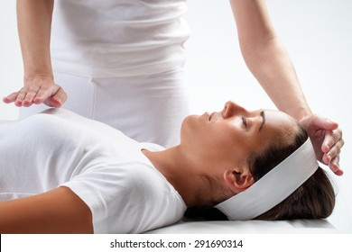 Close up of chiropractors hands doing reiki on young woman.One hand on head and one hand on chest.