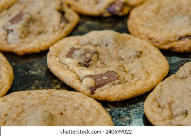 A close up of a chocolate chunk cookie cooling on a granite countertop