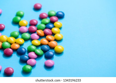 close up of chocolate egg and candy drops on blue background