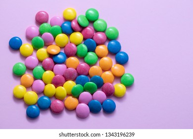 close up of chocolate egg and candy drops on pink background