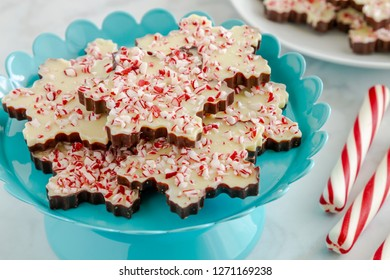 Close up of chocolate peppermint bark in snowflake shape on bright blue metal plate with red and white striped peppermint sticks
