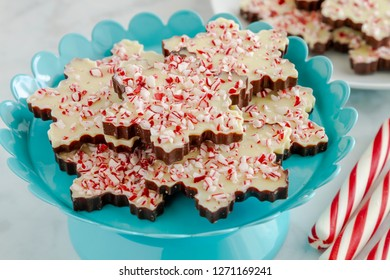Close up of chocolate peppermint bark in snowflake shape on bright blue metal plate and peppermint sticks