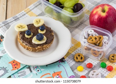 Close up of chocolate spread banana blueberry sandwich with funny face.