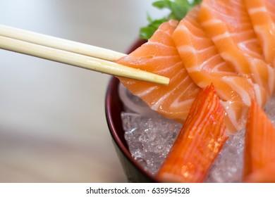 Close up Chopsticks holding Raw Salmon, Salmon Sashimi