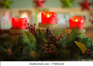 Close up of Christmas centerpiece with three red candles lit and blurred background with colorful stars.