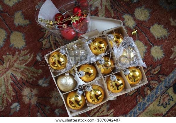 Close up of Christmas decorations in boxes ready to decorate the Xmas green fir tree with selection of gold baubles and wood toys glass antique items on background  carpet in family home  interior