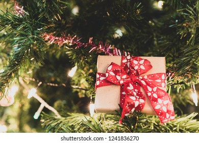 Close up Christmas gift box on pine tree with ribbon and lighting,Christmas background,retro filter