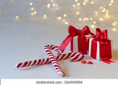 Close up of Christmas gift packages with satin bows and with Christmas lights and colorful fabrics and red striped white candy canes