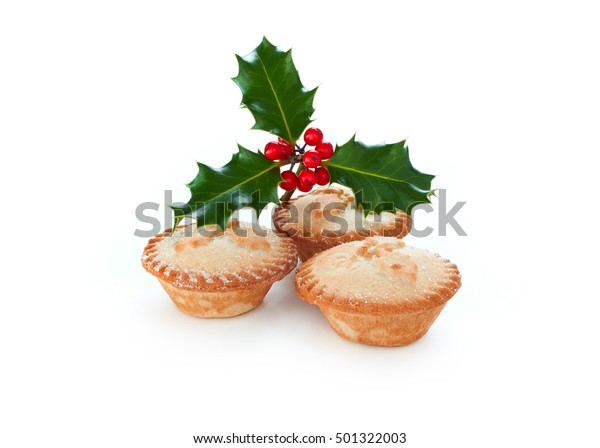 Close up of Christmas Mince Pies and holly sprig isolated on a white background. Sweet Mince Pies, fruit filling.