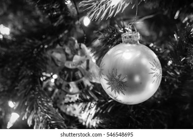 Close up of a Christmas Ornament hanging from a tree in black and white/Silver Ball