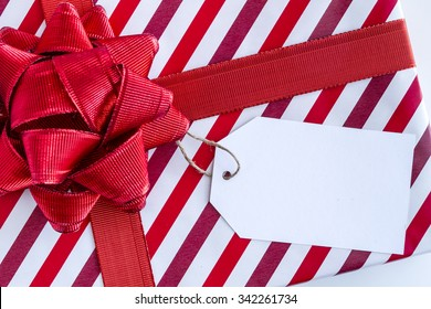 Close up of Christmas present wrapped in red and white striped wrapping paper red ribbon and bow and blank tag sitting on white background