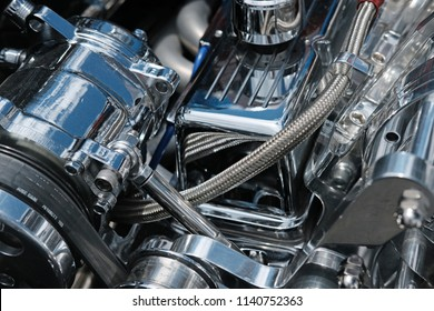 Close up of Chrome Engine Parts, Hoses and Belts on a High Performance Engine