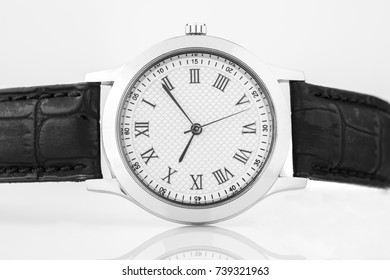 Close up of Chrome Wrist Watch with Roman Numbers and Black Leather Strap Shot in Studio on White Background
