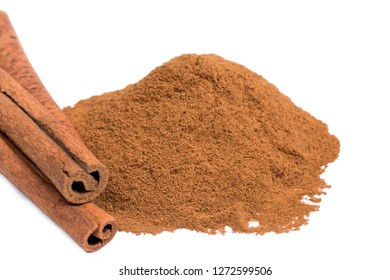 Close up of cinnamon powder and sticks on white background