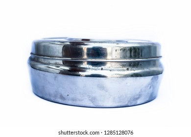 Close up of circular domestic stainless steel container isolated on white used to store, preserve etc.