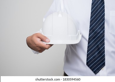 Close up civil engineer holding helmet hard hat standing post in studio on isolated white background. Architecture or engineer concept.