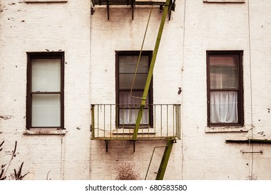 A close up of a classic apartment building with classic fire escape ladder.