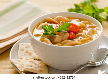 Close up of classic chicken noodle soup with crackers.