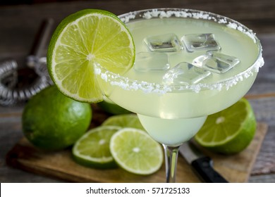 Close up of classic lime margarita cocktail with sliced and whole limes sitting on wooden cutting board