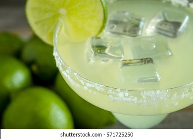 Close up of classic lime margarita cocktail with whole fresh limes in background