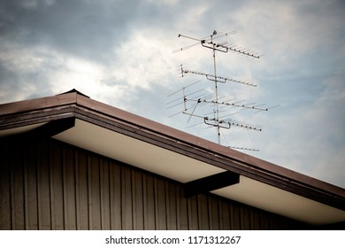 Close up Classic old TV antenna on house roof over cloudy sky