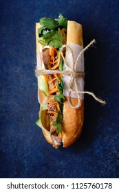 Close up of classical banh-mi sandwich with sliced grilled pork tenderloin, shredded carrots and peeled cucumbers, jalapeno peppers and cilantro on dark blue background