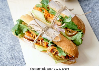 Close up of classical banh-mi sandwich with sliced grilled pork tenderloin, shredded carrots and peeled cucumbers, jalapeno peppers and cilantro