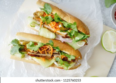 Close up of classical banh-mi sandwich with sliced grilled pork tenderloin, shredded carrots and peeled cucumbers, jalapeno peppers and cilantro on white textured background