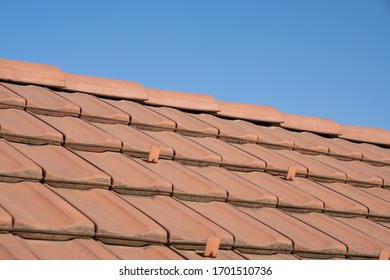 close up of clay roof tiles on a sloping roof underneath a blue sky with copy space