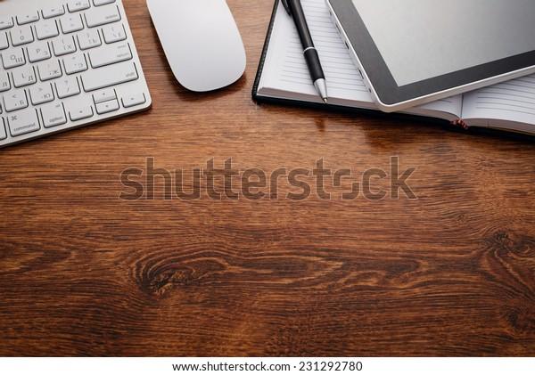 Nahaufnahme von sauberen, offenen Notebooks und elektronischen Geräten wie Tastatur, Maus und Tablet, oben auf dem Holztisch mit Kopienraum unten für Texte.