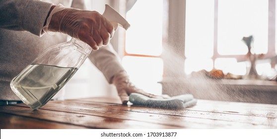 Close up of cleaning home wood table, sanitizing kitchen table surface with disinfectant antibacterial spray bottle, washing surfaces with towel and gloves. COVID-19 prevention sanitizing inside. - Shutterstock ID 1703913877