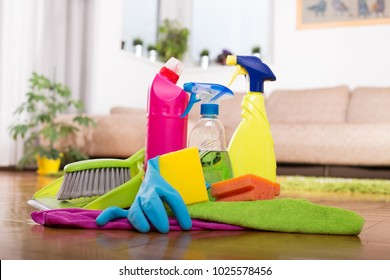 Close up of cleaning products and tools on parquet floor in front of sofa in living room