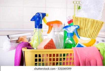 Close up of cleaning supplies and equipment in plastic basket in front of kitchen wall with tiles