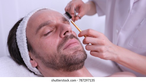 Close Up of Client Man Relaxing while Cosmetician Woman Epilating Eyebrows Using Plucking Tools in Beauty Spa