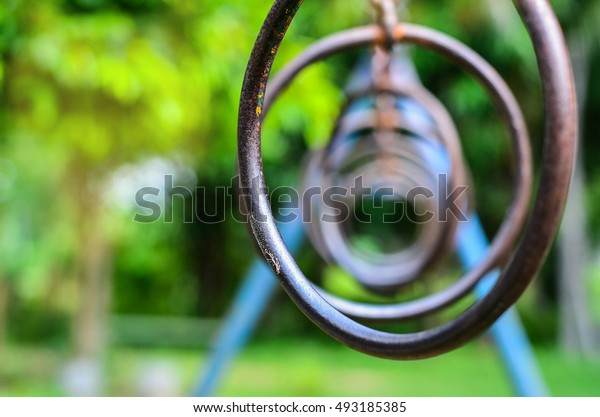 close up Climbing Rings In A Playground.Rusted Iron Ring Fun for kids in playground At rest relaxation with sun light