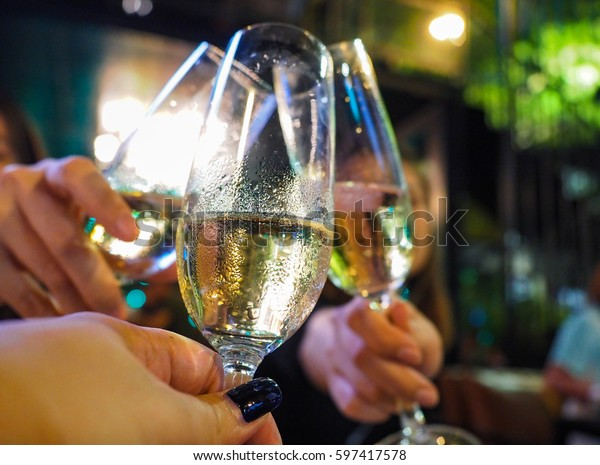 close up clink glasses of white wine at night party at restaurant