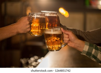 Close up of clinking beer glasses. People resting and having fun in beer house. Clients hanging out on weekends. Meeting of friends in bar.