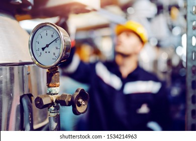Close up of clock on boiler showing pressure on boiler. In background is worker working. Selective focus on clock.