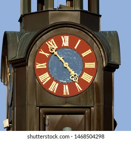 Close up of clock on Lohausschule (Lohau school) in Sonneberg, Germany. golden fingers and numerals on blue/red clock face. Time on clock: 04h53