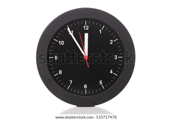 Close up of a clock showing 5 minutes to midnight