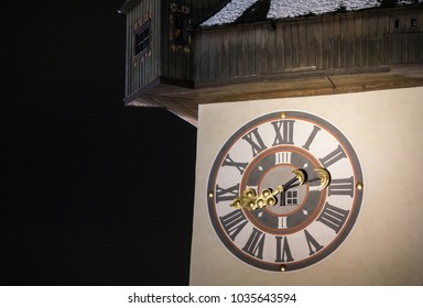 Close up of the clock tower of Graz illuminated at night