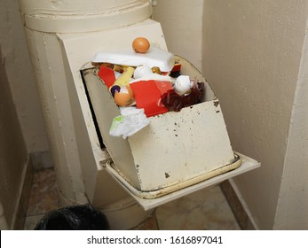 Close up of a clogged with household rubbish chute