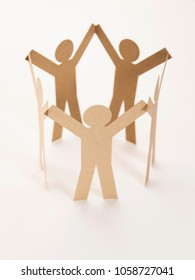 close up of closed joining of five brown paper figure in hand up posture on white background. in concept of cooperation and teamwork