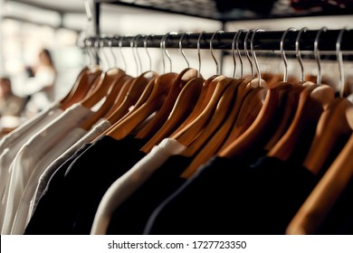 Close up of clothes rack or rail in the store. Items at custom T-shirt, clothing printing company. Horizontal shot