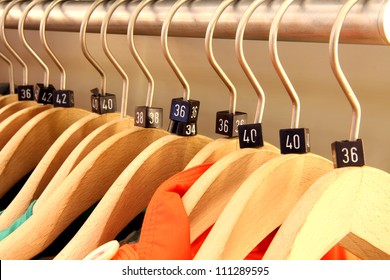 Close up of a clothing rack with wooden hangers showing different European clothing size tags