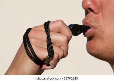 A close up of a coach blowing a whistle