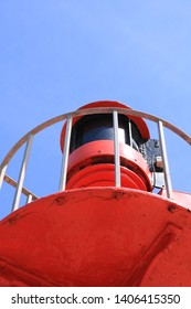 Close up of a coastal viewing platform with a warning light for shipping. Painted a bright coastal red against a deep blue summer sky. Could be used as a coastal home interior picture.
