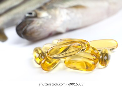 Close up of a  cod liver fish oil capsule, a nutritional supplement high in omega-3 fatty acids, EPA,  DHA, and  high levels of vitamin A and vitamin D.  Fresh fish are in the background.